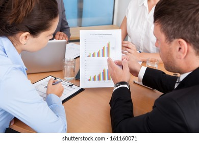 Close-up Of Businesspeople Analyzing Graph Together In Office