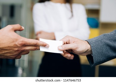 Closeup of businesspeople exchanging business card in the office