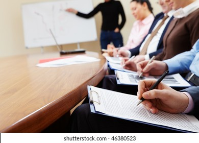 Close-up of businesspeople hands with documents writing at lecture