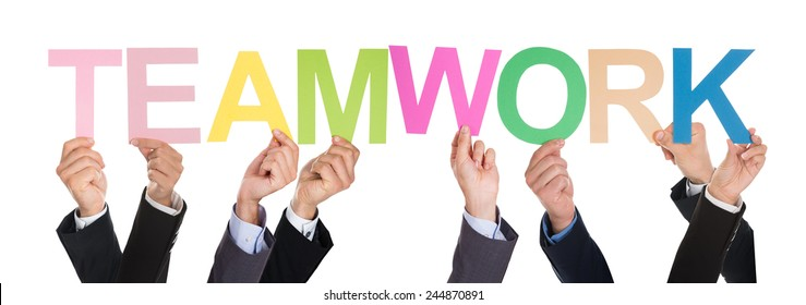 Close-up Of Businesspeople Hands Holding The Word Teamwork