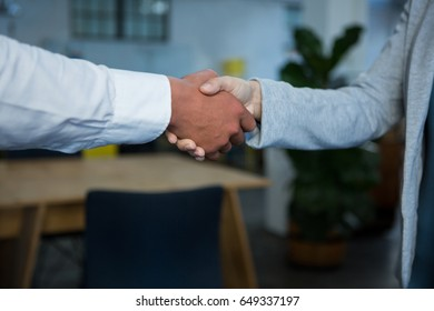 Close-up of businesspeople shaking hands in office