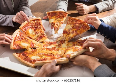 Close-up Of Businesspeople Taking Slice Of Pizza From The Box