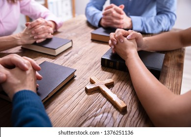 Close-up Of Businesspeople's Praying Hands Over The Bible On Wooden Desk