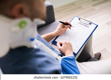 Close-up Of A Businessperson With Broken Arm Filling Health Insurance Claim Form
