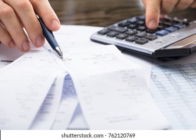 Close-up Of A Businessperson Calculating Receipt With Calculator