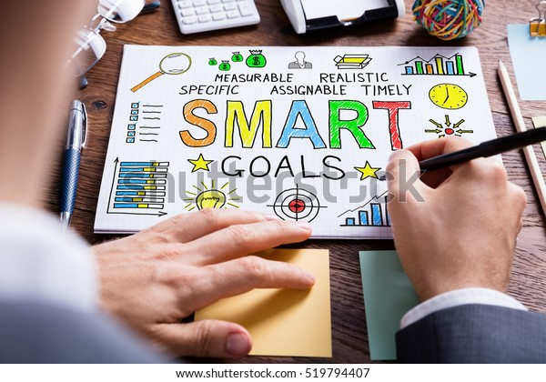 Close-up Of Businessperson Drawing Smart Goal Concept On White Paper On Wooden Desk