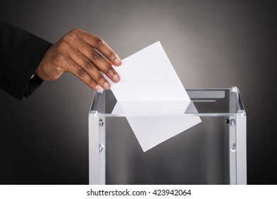 Close-up Of A Businessperson Hand Inserting Ballot In Glass Box Against Gray Background