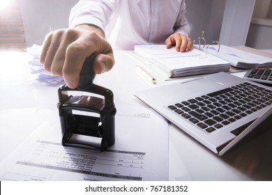 Close-up Of Businessperson Hand Stamping Document On Desk In Office