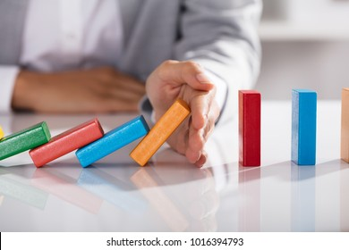 Close-up Of Businessperson Hand Stopping Colorful Blocks From Falling On Table In Office