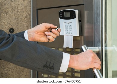 Close-up Of Businessperson Hand Using Remote Control For Operating Door In Security System