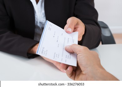 Close-up Of Businessperson Hands Giving Cheque To Other Person At Desk
