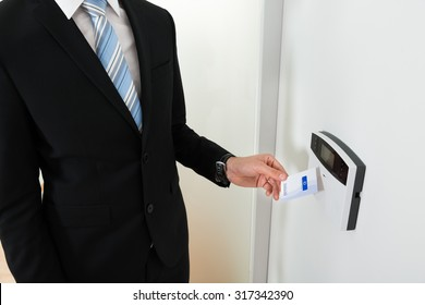 Close-up Of Businessperson Hands Holding Keycard To Open Door