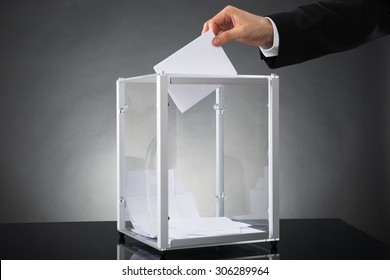 Close-up Of Businessperson Hands Putting Ballot In Box At Desk