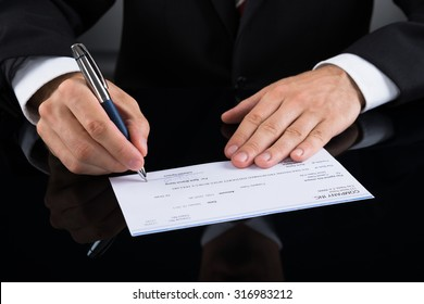 Close-up Of Businessperson Hands Signing Cheque With Pen