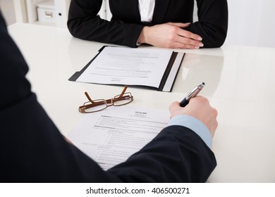 Close-up Of Businessperson Holding Pen Over Resume In Office