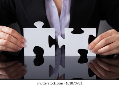 Close-up Of Businessperson Holding Two Puzzle In Hand