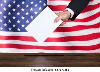 Close-up Of A Businessperson Inserting Ballot In Box In Front Of American Flag