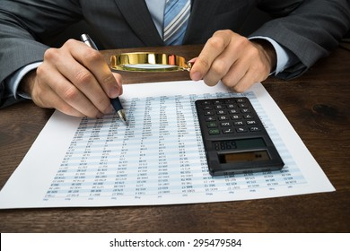 Close-up Of Businessperson Inspecting Financial Data With Magnifying Glass