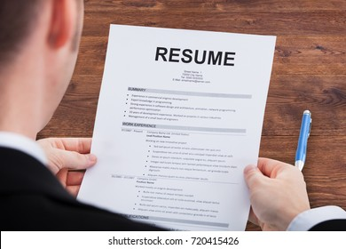 Close-up Of A Businessperson Looking At Resume Over Wooden Desk