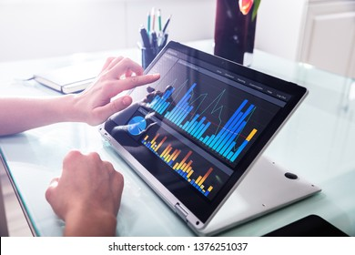 Close-up Of Businessperson Pointing At Graph On Digital Laptop In Office
