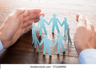 Close-up Of Businessperson Protecting Cut-out Figures On Wooden Desk