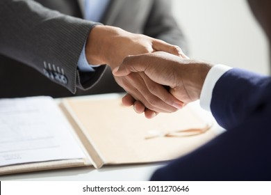 Close-up Of Businessperson Shaking Hand With Candidate At Workplace