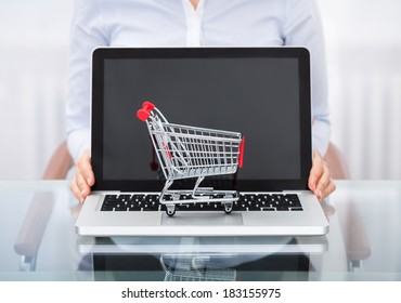 Close-up Of Businessperson With Shopping Cart Over A Laptop