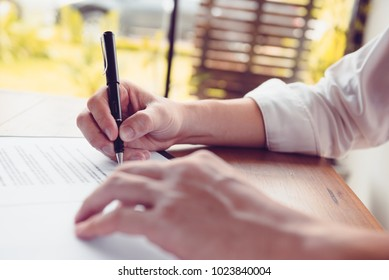 Close-up Of Businessperson Signing Contract, man writing paper at the desk with pen and reading books at table with basic business Form document working in office