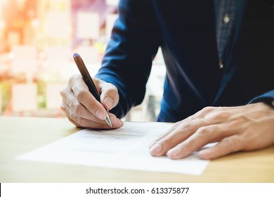 Close-up Of Businessperson Signing Contract,woman writing paper at the desk with pen and reading books at table with basic business Form document working in office