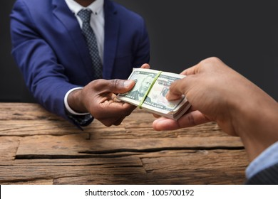 Close-up Of Businessperson Taking Bribe From Partner On Wooden Desk