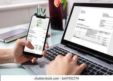 Close-up Of Businessperson Using Laptop While Paying Invoice On Mobilephone In Office