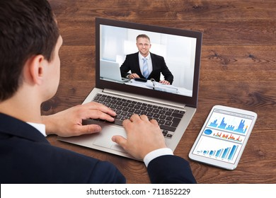 Close-up Of A Businessperson Video Conferencing With Male Colleague On Laptop