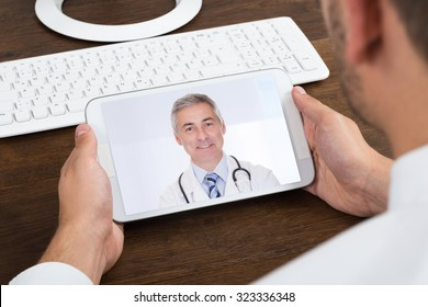 Close-up Of Businessperson Videochatting With Senior Doctor On Mobile Phone