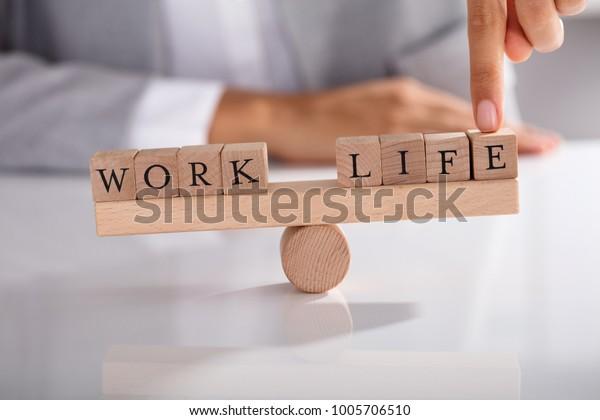 Nahaufnahme des Fingers von Geschäftsleuten, die ein Ungleichgewicht zwischen Arbeit und Leben auf Holz zeigt Seesaw