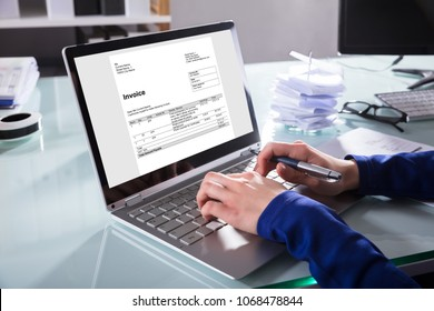 Close-up Of A Businessperson's Hand Analyzing Invoice On Laptop At Workplace