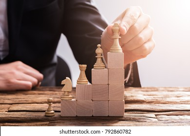 Close-up Of A Businessperson's Hand Arranging Chess Piece On Wooden Blocks