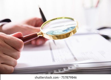 Close-up Of A Businessperson's Hand Calculating Bill With Magnifying Glass