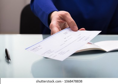 Close-up Of A Businessperson's Hand Giving Cheque