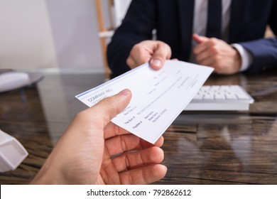 Close-up Of A Businessperson's Hand Giving Cheque To Colleague At Workplace