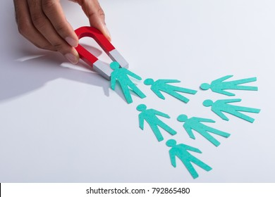Close-up Of A Businessperson's Hand Holding Red Horseshoe Magnet Attracting Paper Candidates On Desk