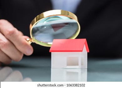 Close-up Of A Businessperson's Hand Looking At House Model Through Magnifying Glass