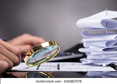 Close-up Of A Businessperson's Hand Looking At Invoice Through Magnifying Glass At Workplace