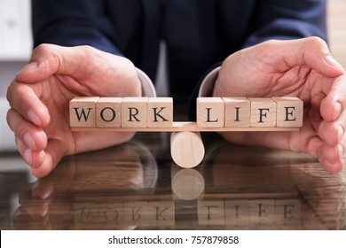 Close-up Of A Businessperson's Hand Protecting Balance Between Life And Work On Seesaw Over Desk