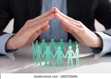Close-up Of A Businessperson's Hand Protecting Blue Paper Cut Out Figures On White Background
