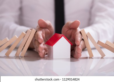 Close-up Of A Businessperson's Hand Protecting House Model From Falling Wooden Blocks On White Desk