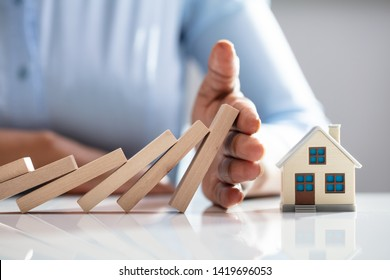 Close-up Of A Businessperson's Hand Protecting House Model From Falling Wooden Blocks On Desk