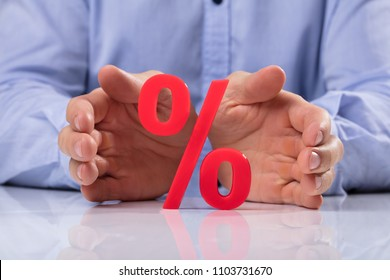 Close-up Of A Businessperson's Hand Protecting Red Percentage Sign