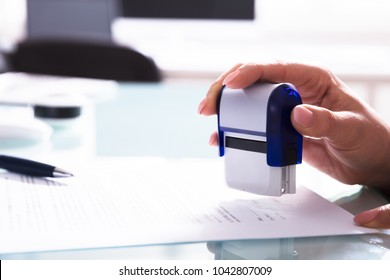 Close-up Of A Businessperson's Hand Stamping Document At Workplace