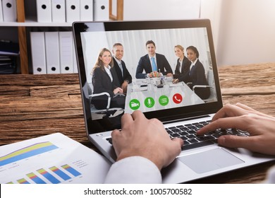 Close-up Of A Businessperson's Hand Video Conferencing With Colleagues On Laptop