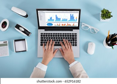 Close-up Of A Businesswoman Analyzing Various Graphs On Laptop On Blue Desk In Office